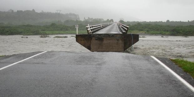 The washed out section of the Wanganui River bridge near Harihari. Photo / Hokitika Guardian