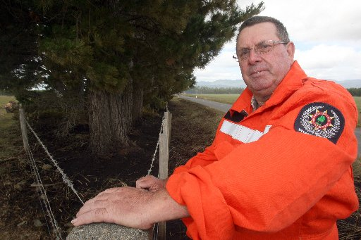 RISKY BUSINESS: Rural fire officer Porky Sexton at the scene of a blaze that broke out in a shelter belt of pines on the East West Access Rd in rural Featherston after high winds carried embers to the trees from a controlled burn-off on a nearby farm.