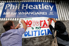 Primary school teachers fix signs to the wall outside Whangarei MP Phil Heatley's office during this morning's nationwide protest. Photo / John Stone