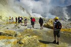 Tourists make their way through the crater of the volcano on White Island. Photo / Alan Gibson