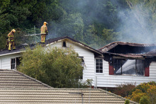 Firefighters work on the house that caught fire on Woodhouse Avenue, Karori, Wellington. Photo / Mark Mitchell
