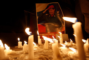 Candles, placed by mourners, burn in front of an image of the late President Hugo Chavez outside Venezuela's embassy in Quito, Ecuador.  Photo / AP