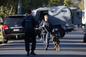 Police with a dog move on the street during the siege in Glenroy. Photo / Hamish Blair