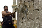 Kadom al-Jabouri swings a hammer at a statue of Saddam Hussein in downtown Bagdhad. Photo / AP