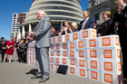 Grey Power president Roy Reid presenting the Keep Our Assets citizens initiated referendum petition to Opposition politicians at Parliament in March. Photo / Mark Mitchell