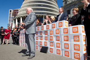 Grey Power president Roy Reid presenting the Keep Our Assets citizens initiated referendum petition to Opposition politicians at Parliament. Photo / Mark Mitchell