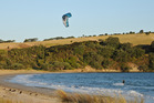 A kite-surfer zooms past at Te Haruhi Bay, Shakespear regional park. Photo / Liz Light