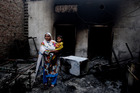 A Christian woman surveys the charred remains of her home. Photo / AP