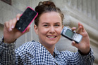 Helen Griffen is finding life harder after turning to a Nokia mobile (right) to replace her old iPhone, similar to the one she's holding. Photo / Sarah Ivey