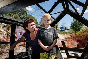 Head teacher Shelly Prisk with a very disappointed 3-year-old Dearne Fowler inside the burnt out whare. Photo / John Stone