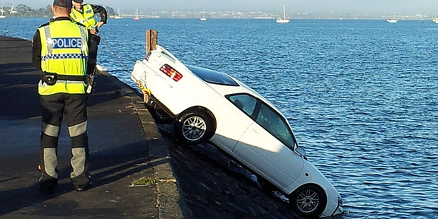 Loading Police winch a car out of the water after a driver accidentally reversed it into the Waitemata Harbour. Photo / Leighton Spurdle/Supplied