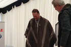 John Key received a poncho from farm manager Alberto Cussens. Photo / Claire Trevett