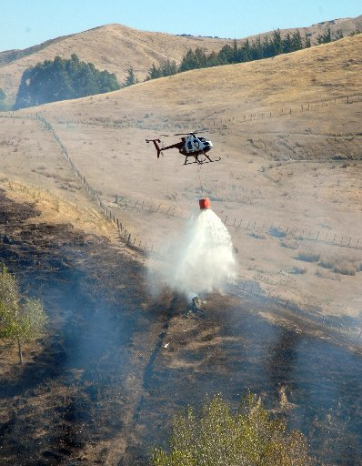One of two Amalgamated Helicopters machines dumps water drawn from a nearby farm dam on to hotspots left in the wake of a blaze that erupted soon after 12pm in a roadside pine plantation on Whangaehu Valley Rd northeast of Masterton.