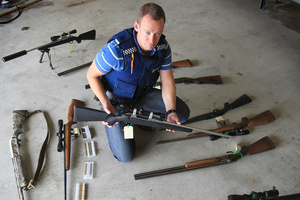 Tim Bonner, Tauranga constable, with the firearms seized after his investigation into a widespread poaching ring. Photo / Bay of Plenty Times