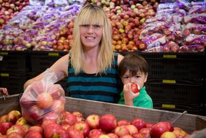 Sandie Speeden, with Micah, 3, took home 5kg of Royal Gala apples for 45c. Photo / John Cowpland