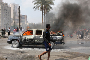 An Egyptian walks by a burning police vehicle in Tahrir Square. Photo / AP