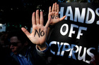 Protesters hold up their hands as they protest outside the parliament in capital Nicosia, Cyprus. Photo / AP