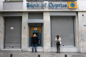 Customers of Bank of Cyprus use the ATM in central Athens. Photo / AP