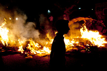 An Egyptian activist walks past burning tires during an anti Muslim Brotherhood protest. Photo / AP