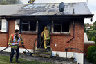 Firefighters begin dampening down hot spots following a house fire in Mornington. Photo / Peter McIntosh