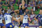 Billy Slater of the Storm catches a high ball and kicks David Klemmer of the Bulldogs. Photo / Getty Images