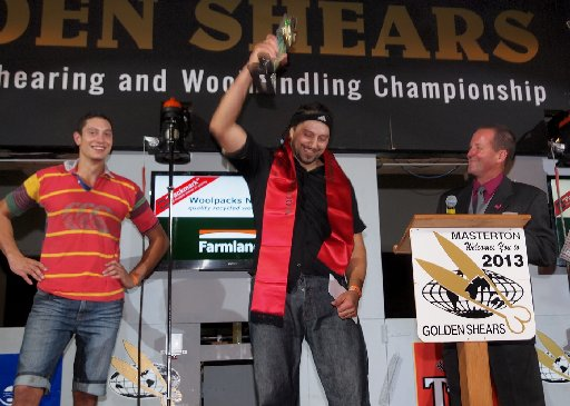 Golden Shears Friday night finals. Defending world champion wool-presser Jeremy Goodger, of Masterton holds aloft his 2013 winning trophy.