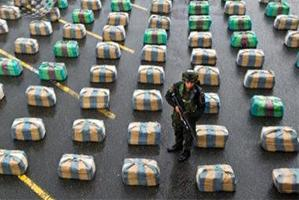 A Colombian police officer stands guard next to packages with 7.7 tons of seized marijuana.  Photo / AFP