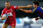 Quade Cooper of the Reds fends off Elliot Dixon of the Highlanders during the round seven Super Rugby match between the Highlanders and the Reds. Photo / Getty Images.