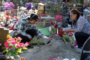 Lachan Kelly-Tumarae's grandmother Narina Tumarae (right) and cousin Gilbert Tumarae lay tributes at his grave, two years after the teenager was fatally shot by police. Photo / Duncan Brown