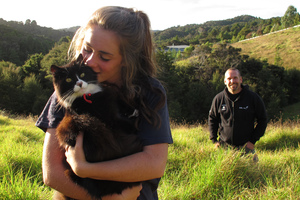 Sixteen-year-old Phoenix Bright-Young with Lucky the cat and Bay Bush Action trustee Craig Salmon with the Opua State Forest in the distance. Lucky is one of the first cats to get a free bell collar from Bay Bush Action, an initiative to protect Northland's birdlife.  Photo / Peter De Graaf