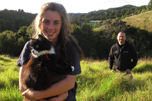 Sixteen-year-old Phoenix Bright-Young with Lucky the cat and Bay Bush Action trustee Craig Salmon with the Opua State Forest in the distance. Photo / APN