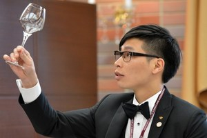 Taiwanese contestant Thomas Ho checks a glass before serving wine to judges during the quarter-final of the 14th world sommelier contest in Tokyo.Photo / AFP