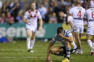 Beau Ryan of the Sharks looks dejected as Dragons players celebrate victory. Photo / Getty Images