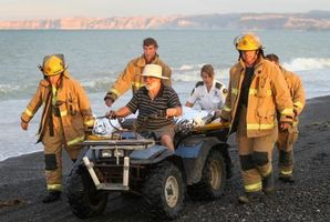 Fire service and St John Ambulance staff carefully bring a 13 year-old boy off the beach with the help of Andrew Garland riding the quad bike. Photo / Duncan Brown