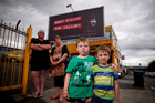 Roger and Caroline Callow with grandchildren Ali (7) and Max (5) below the billboard featuring son Ken, who died in a forestry mishap.  Photo / Dean Purcell