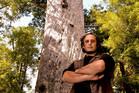 Will Ngakuru with the Tane Mahuta kauri tree at Waipoua Forest. Photo / Malcolm Pullman