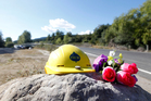 A construction hat and flowers by the side of the road in memory of George Taiaroa. Photo / Christine Cornege