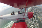 Nicholas Jones gets an elevated view of the Gold Coast with Geoff Stillman, of Tiger Moth Joy Rides. Photo / Supplied