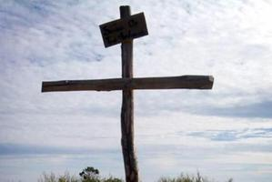 The large make-shift cross made out of a fence posts bearing a plywood sign. Photo / Supplied