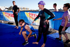 TVNZ's Breakfast presenter Toni Street (right) tags her co-host Rawdon Christie as he gets ready for the bike leg during the sprint triathlon held in downtown Auckland yesterday. Photo / Dean Purcell
