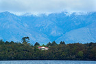Grand View House on the shores of Lake Manapouri is dwarfed by the mountains behind. Photo / Supplied
