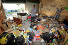Landlord Myra Williams stands among the rubbish left in her Gonville rental property's garage after her tenants moved out. Photo / Stuart Munro