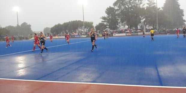 Players run from the field in heavy rain. Photo / @BlackSticks