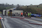 The truck rolled shortly before 4.30am, spilling gas cylinders onto the road. Photo / Alan Gibson