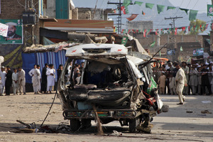 Pakistanis gather at the site of a bomb explosion in Peshawar. Photo / AP