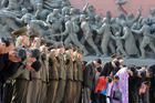 Military personnel salute as civilians bow to giant statues of the late North Korean leaders, Kim Il Sung and his son Kim Jong Il. Photo /AP