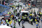 Medical workers aid injured people at the finish line of the 2013 Boston Marathon following the explosions. Photo / AP