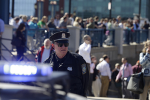A Boston police officer stands guard as people stand on a bridge outside the John Joseph Moakley Federal Courthouse. Photo / AP