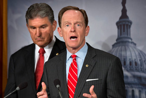 Senator Joe Manchin (left) listens as Senator Patrick Toomey announces they have reached a deal on expanding checks on gun buyers. Photo / AP