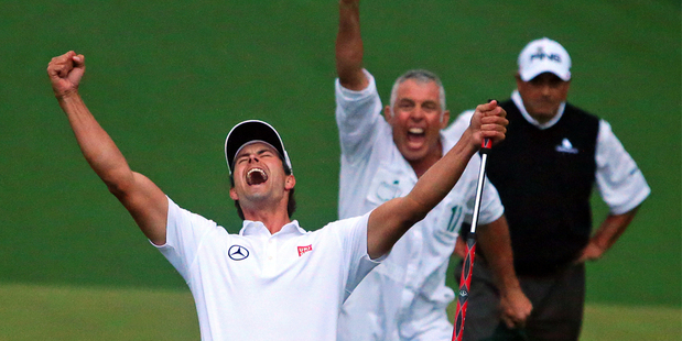 Adam Scott celebrates winning the US Masters, with caddie Steve Williams in the background and playoff runner-up Angel Cabrera behind him. Photo / AP
